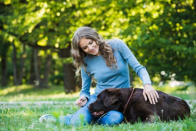 美しい女性が庭で彼女の犬を叩く