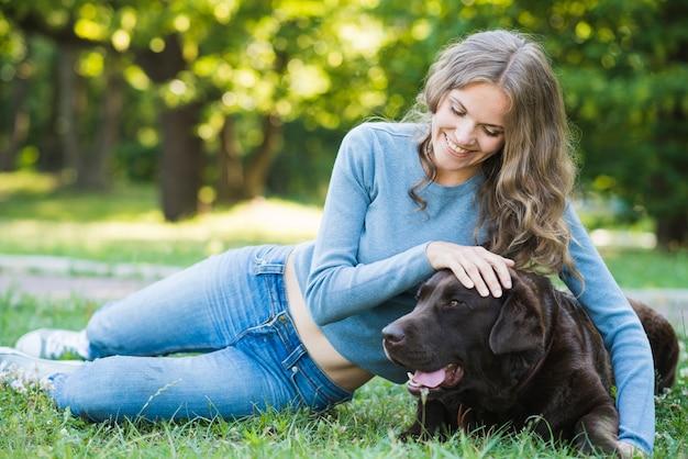 緑の草の上に犬に抱く幸せな若い女性の肖像画