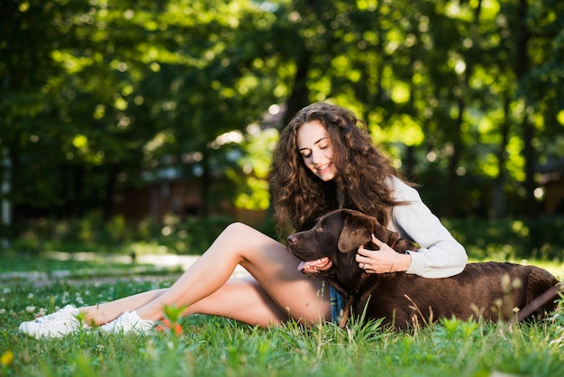 公園の草の上に座っている彼女の犬を叩く女性