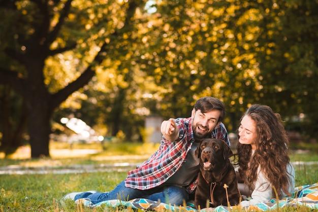 彼の犬とガールフレンドと公園に何かを見せている男