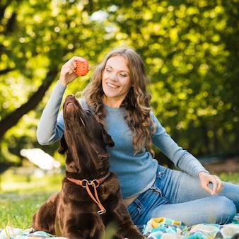 庭で彼女の犬と遊んでいる幸せな女性