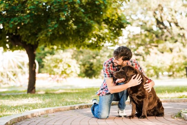 公園の歩道に彼の犬を持つ男