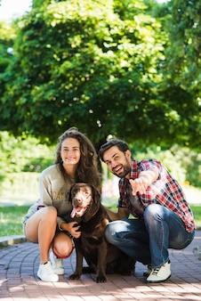 Счастливая молодая пара с собакой в саду