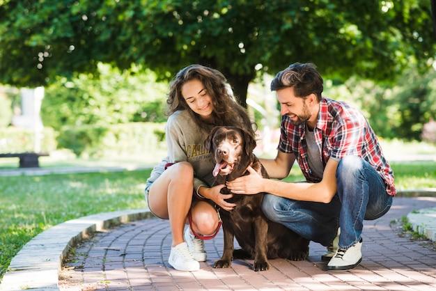 Портрет пары с собакой в парке