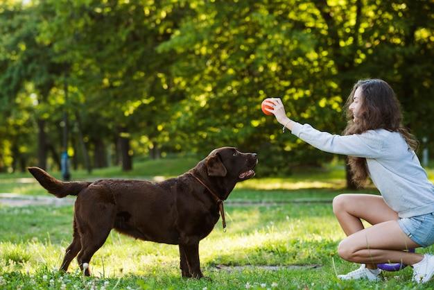 Женщина, с удовольствием со своей собакой в саду