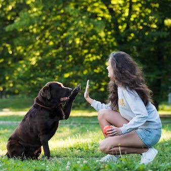 Женщина дает пятерку собаке