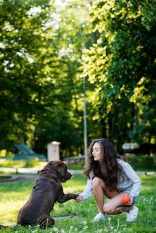庭に彼女の犬の足を振っている女性