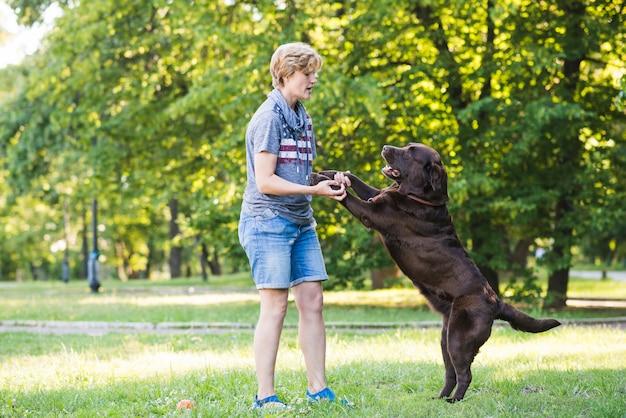 公園で彼女の犬と遊んでいる成熟した女性の側面図