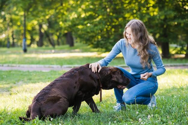 庭で彼女の犬を撫でている幸せな女性