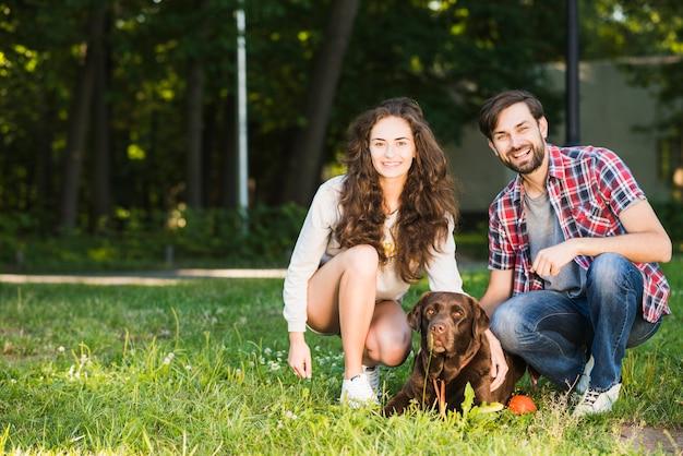 公園での犬と幸せな若いカップルの肖像