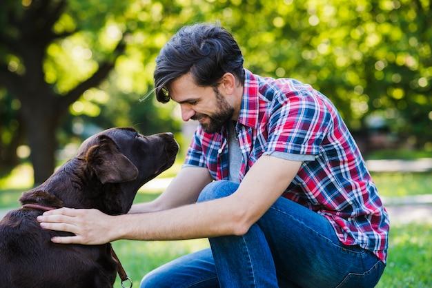 彼の犬を見ている若い男の側面図