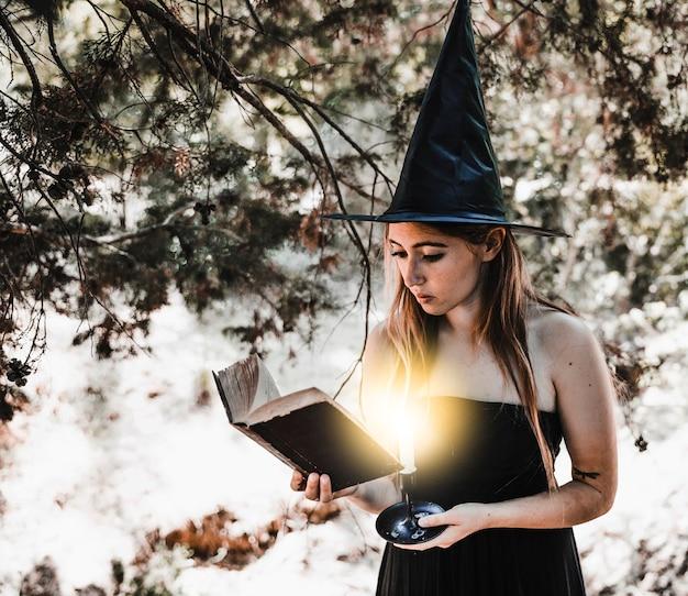 Молодая женщина в шляпе ведьма, чтение книги в лесу