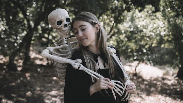 瞬きの女性の後ろに抱かれたスケルトン