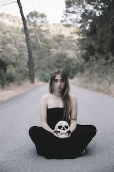 道路に座っている頭蓋骨を持つ若い女性