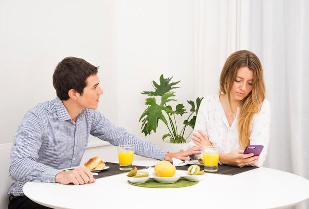 携帯電話を使っている彼女の悲しいガールフレンドについての男