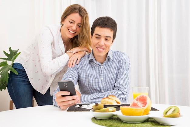 Улыбается молодая пара, глядя на мобильный телефон за столом для завтрака
