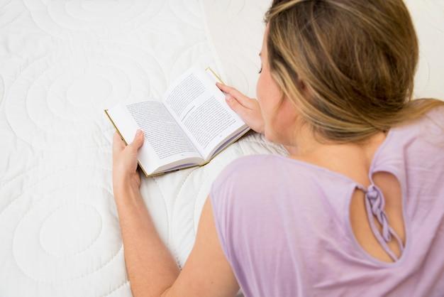 Вид сверху молодой женщины, читающей книгу на кровати