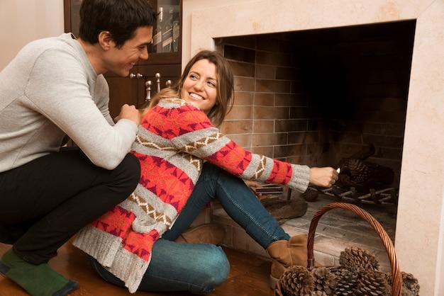 若い女性を見ている男は、暖炉で大きな試合を点火