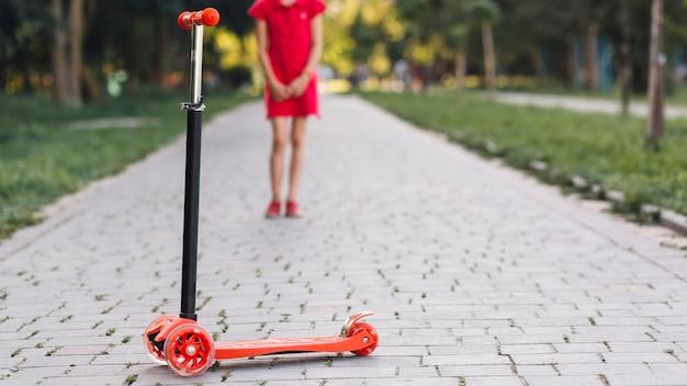 公園の歩道に立っている女の子の前でスクーターを押す