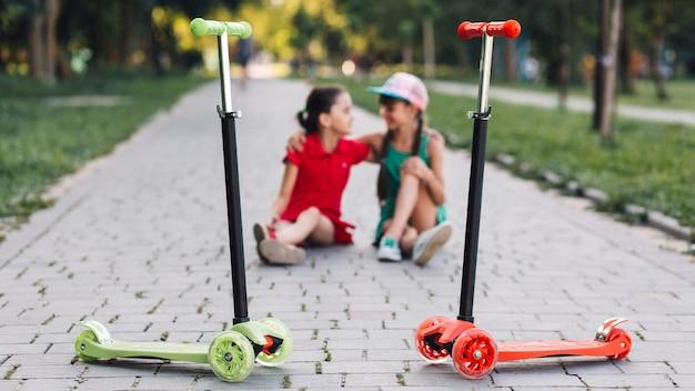 公園の歩道に座っている女の子の前でスクーターを押す