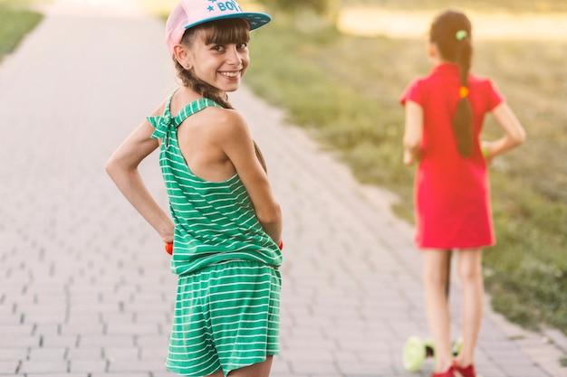 背中を見るプッシュスクーターに立っている笑顔の女の子の肖像