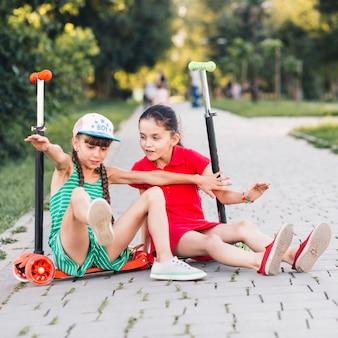 公園で楽しんでいる蹴ったスクーターに座っている女の子