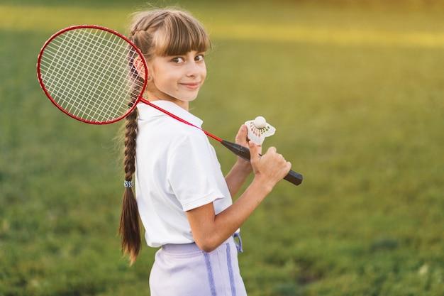 彼女の肩とシャトルコックの上にバドミントンを持っている笑顔の女の子