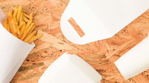木製の背景にフライドポテトと白いパッケージのオーバーヘッドビュー