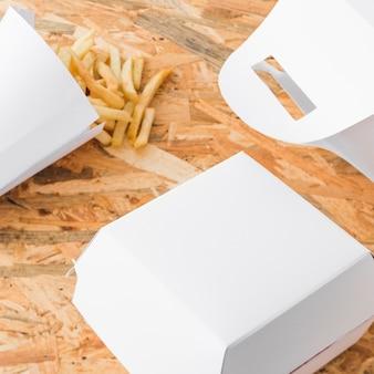木製の机の上でフライドポテトと食品小包のモックアップの高い角度のビュー