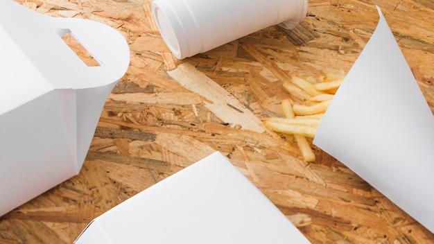 木製の背景に処分用カップと食品小包をモックアップ