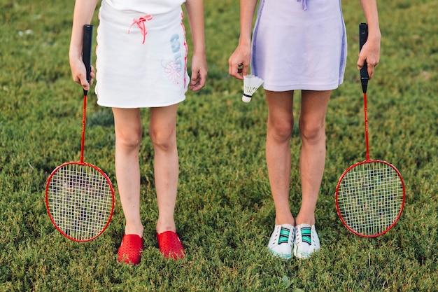 バドミントンとシャトルコックを保持している緑の草に立っている女の子の低い部分
