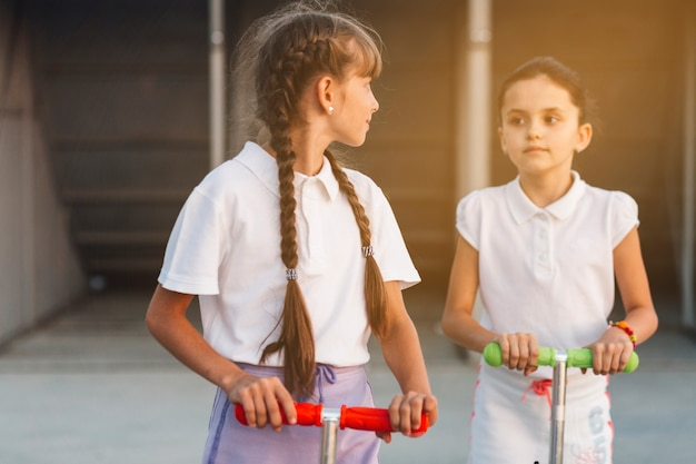 スクーターに乗っている彼女の友達を見ている少女