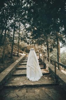 Человек в костюме призрак идет по лестнице