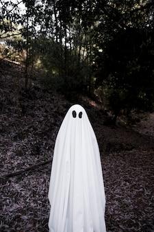 Человек в костюме призрак, стоящий в парке