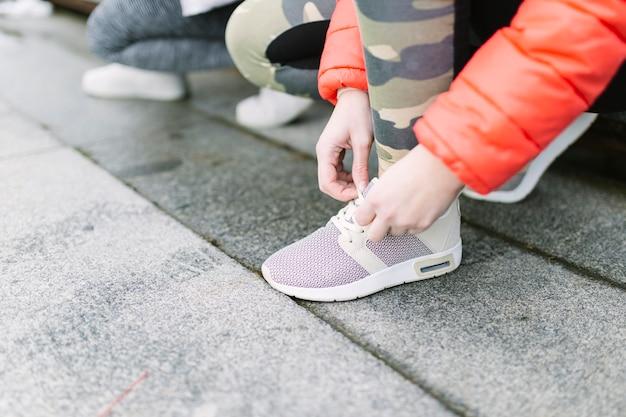Крупный план бегуна, связывающего шнурки