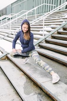 Молодая женщина улыбается растяжения ноги на шаги