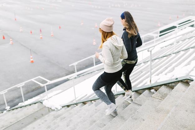 Две женщины бегают по лестнице зимой