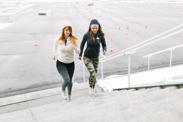 Два женских бегуна бегают по лестнице зимой