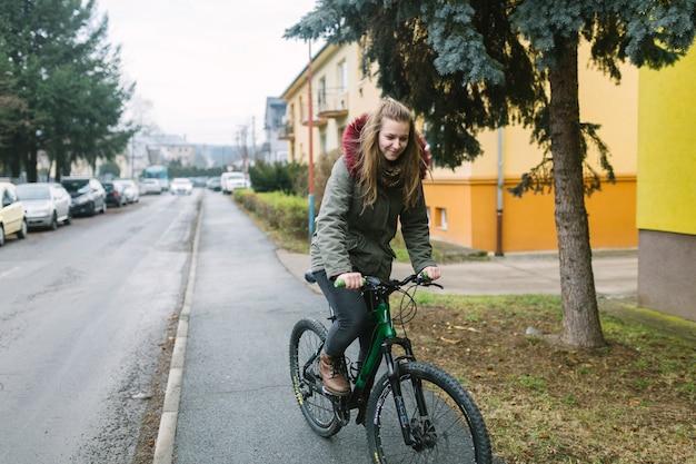 都市の道路にブロンドの若い女性が乗る自転車
