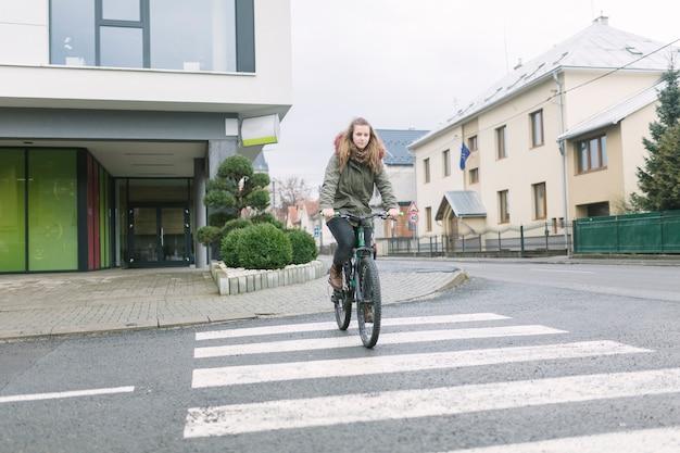フード付きのトップライディング自転車を着て街中でブロンドの若い女性