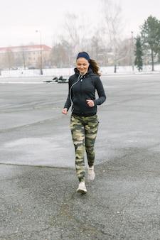 ストリートで走っている女性フィットネスアスリート