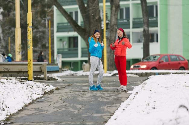 Две женщины бегун, стоя на улице в зимний сезон, давая пальцем вверх знак
