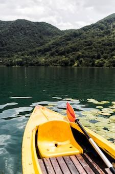 山の近くの湖の空のカヌーのクローズアップ