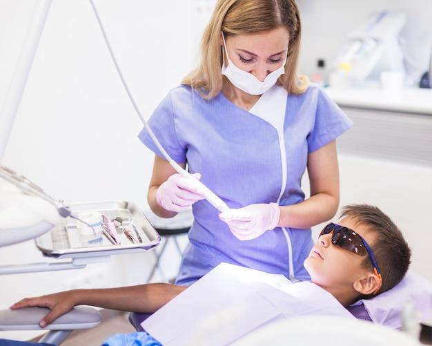 歯科医は超音波スケーラーを使って診察室の少年の歯を治療する