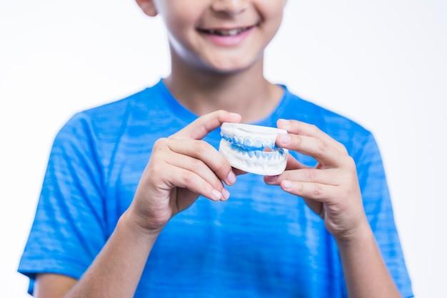 歯の石膏型を保持している男の子の手のクローズアップ