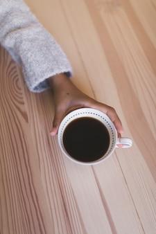 木製の机の上にコーヒーのカップを持つ手のクローズアップ