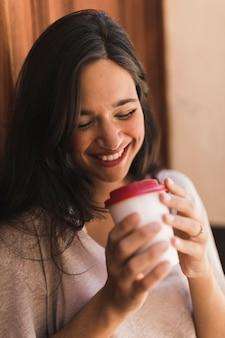 使い捨てコーヒーカップを持っている笑顔の女の子の肖像