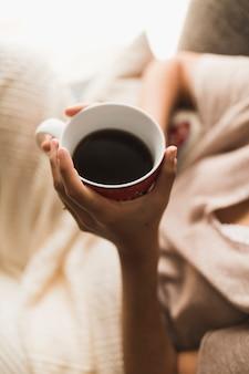 コーヒーカップを手に持っている女の子のオーバーヘッドビュー