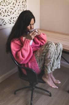 Девочка-подросток, сидя на стуле, пить кофе дома