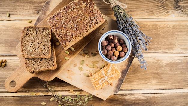 チョッピングボード上のタンパク質バーを持つボウル内の全粒パンとヘーゼルナッツの上面図